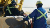 A crew of pipeline workers install a quick coupler on a tailings pond line.