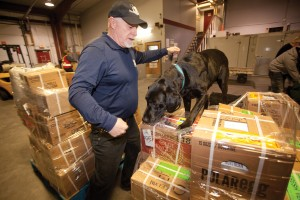 Dog-handler Mark Hicks leading a black Labrador retriever named OD (short for Over Dose) through his paces, sniffing luggage and freight for drugs and alcohol before the cargo flight heads north. (Bill Braden photo).
