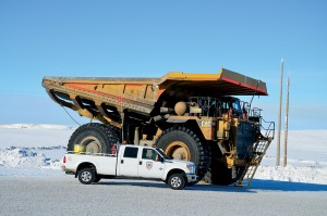 A Scarlet Security pick-up truck is dwarfed by a huge off-road hauler on Canada's ice highway.